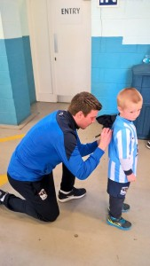Chris Stokes signs a shirt for a young fan